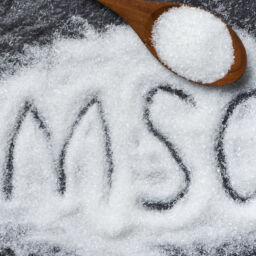 Heap of monosodium glutamate on wooden spoon and dark background with text MSG